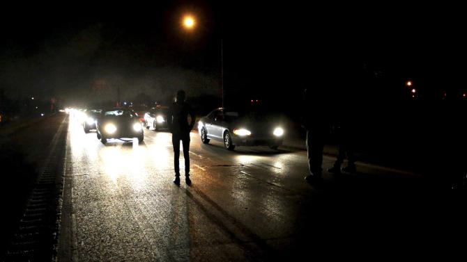 Protesters shut down an interstate at Airport Road on Wednesday, Dec. 24, 2014, in Berkeley, Mo. Demonstrators took to the streets for a second night after a white police officer in Berkeley, Mo., killed a black 18-year-old who police said pointed a gun at him. (AP Photo/St. Louis Post-Dispatch, Robert Cohen)
