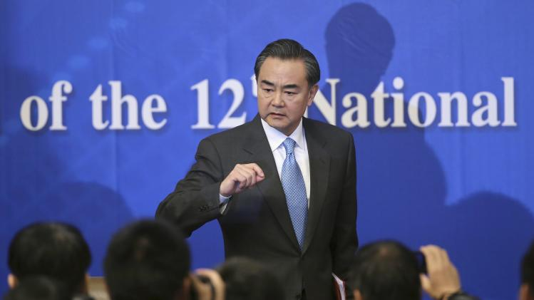 China's Foreign Minister Wang Yi gestures to journalists as he leaves a news conference as part of the NPC in Beijing