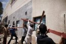 Protesters break the windows of the U.S. embassy in Sanaa