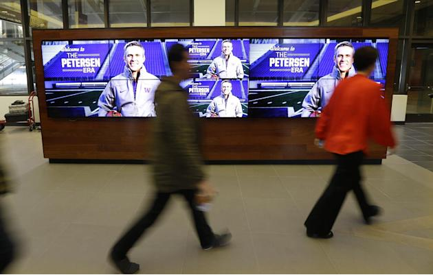 People walk past a video display announcing the hiring of Chris Petersen as the new head football coach at the University of Washington, Monday, Dec. 9, 2013, in Seattle. Petersen formerly was head co