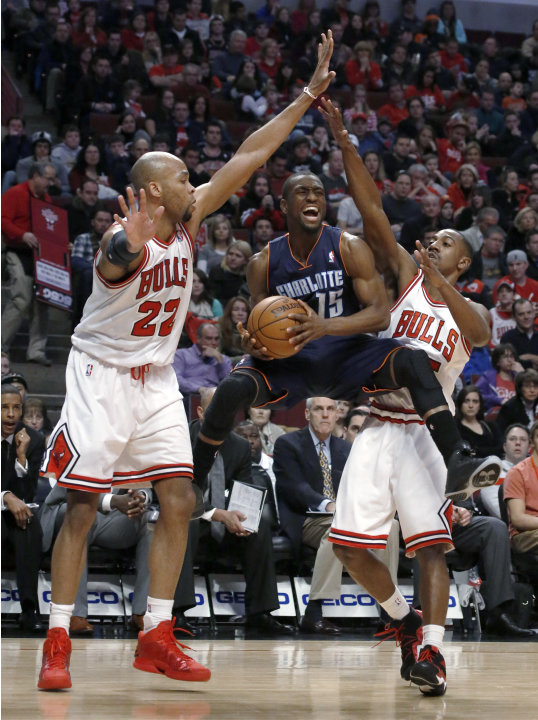 Charlotte Bobcats guard Kemba Walker (15) splits the defense of Chicago Bulls'Taj Gibson (22) and Marquis Teague during the first half of an NBA basketball game Monday, Dec. 31, 2012, in Chicago. (AP