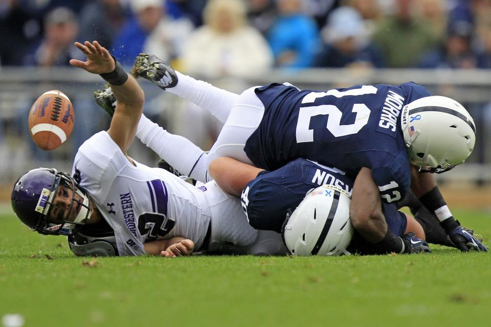 Northwestern quarterback Kain Colter (2) is tackled by Penn State cornerback Stephon Morris (12) and linebacker Glenn Carson (40) as he attempts to catch a pass during the second quarter of an NCAA college football game in State College, Pa., Saturday, Oct. 6, 2012. (AP Photo/Gene J. Puskar)