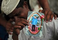 Aziz Ahmed, father of Asif Aziz who was killed in the garment factory fire holds his son's picture in Karachi