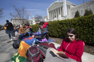 In this photo taken Saturday, March 23, 2013, Jessica Skrebes of Washington reads while waiting in line with others outside of the U.S. Supreme Court in Washington in anticipation of Tuesday's Supreme Court hearing on California's Proposition 8 ban on same-sex marriage, and Wednesday's Supreme Court hearing on the federal Defense of Marriage Act, which defines marriage as the union of a man and a woman. (AP Photo/Jacquelyn Martin)