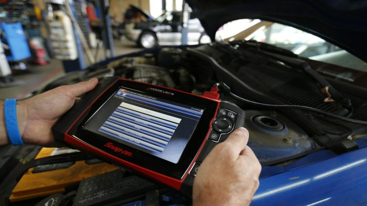 Mechanic John Eppstein uses a basic hand held computer to try and diagnose a vehicle in for repair at his garage in San Diego, California