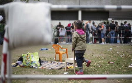 Migrants wait in front of the State Office for Health and Social Affairs (LaGeSo), in Berlin