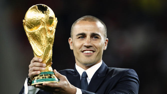 FILE - In this  Sunday, July 11, 2010 file photo Fabio Cannavaro displays the World Cup trophy before the World Cup final soccer match between the Netherlands and Spain at Soccer City in Johannesburg, South Africa. Italy's winning World Cup captain Fabio Cannavaro is reportedly under investigation for tax evasion. Local media report Wednesday Oct. 22, 2014 that nearly one million euros (more than $1 million) worth of goods linked to Cannavaro were sequestered by tax police in his hometown of Naples. Without providing details, Italy's tax agency confirmed the reports. A statement from Cannavaro's lawyers said that the inquiry involves a company owned only by the player's wife, adding that the couple is convinced it did no wrong. (AP Photo/Bernat Armangue, file)