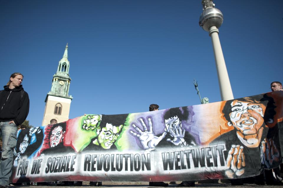 Protestors carry a banner that calls for a world-wide social revolution during a demonstration to support the ' Occupy Wallstreet' movement in Berlin , Saturday Oct. 15, 2011. Protestors gathered at many major European cities Saturday to join in demonstrations against corporate greed and inequality. (AP Photo/dapd, Axel Schmidt)