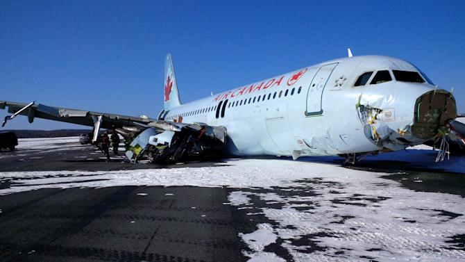"""This photo provided by the Transportation Safety Board of Canada shows a Air Canada Airbus A-320 at Halifax International Airport after making an """"abrupt"""" landing and skidding off the runway in bad weather early Sunday, March 29, 2015. Officials said 23 people were taken to a hospital for observation and treatment of minor injuries, none of which were considered life threatening. (AP Photo/The Transportation Safety Board of Canada)"""