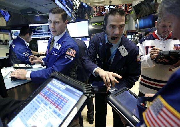 FILE - In this Friday, Feb. 21, 2014, file photo, trader Gregory Rowe, center, works at the post of specialist Joseph Mastrolia, left, on the floor of the New York Stock Exchange. The mood in financia