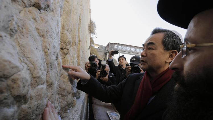 Chinese Foreign Minister Wang stands next to Western Wall Rabbi Rabinovitch as he touches the stones of the Western Wall during his visit in Jerusalem's Old City