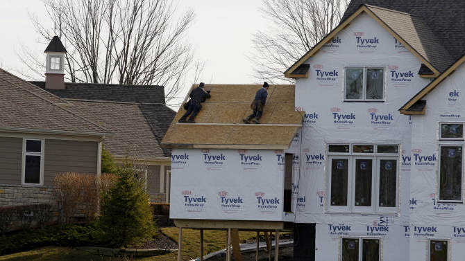 This Thursday, Dec. 6, 2012 photo, shows construction workers framing a new home in Pepper Pike, Ohio. Chemical and bioscience company DuPont Co. says weakness in its performance chemicals and electronics and communications businesses, coupled with costs associated with growth initiatives, led to a sharp drop in fourth-quarter income. (AP Photo/Tony Dejak)