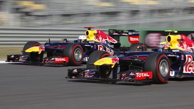 Red Bull Formula One driver Sebastian Vettel (L) of Germany drives alongside team mate Mark Webber of Australia during the second practice session of the South Korean F1 Grand Prix at the Korea International Circuit in Yeongam October 12, 2012.