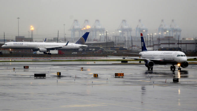 A plane, left, lands at Newark Liberty International Airport as another plane taxis, Thursday, Dec. 27, 2012 in Newark, N.J. An overnight storm caused minor delays at the airport. (AP Photo/Julio Cortez)