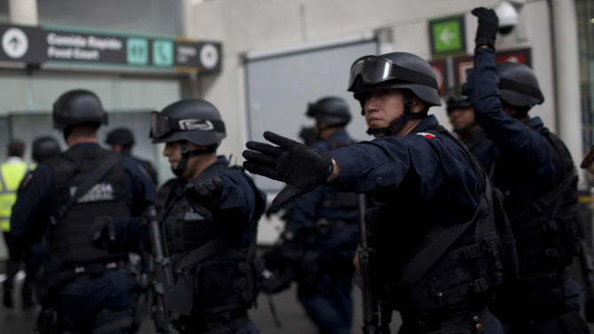 Mexico's Federal Police officers arrive to the scene where a shooting took place in Mexico City's international airport on Monday, June 25, 2012. Two people were shot to death and one was wounded at one of the airport's terminal and according to the federal Public Safety Department, at least one was an officer. Details of the shooting are still unclear. (AP Photo/Alexandre Meneghini)