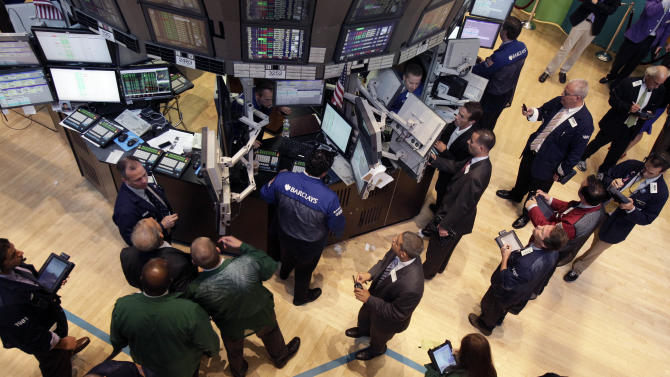 Traders and floor officials gather at a post on the floor of the New York Stock Exchange shortly after the beginning of trading, Wednesday, Aug. 1, 2012. The market wavered between gains and losses for much of Wednesday, yanked around by technical problems, an ambiguous statement from the Federal Reserve, and mixed reports on U.S. companies that made it difficult to decipher just where the economy is headed.  (AP Photo/Richard Drew)