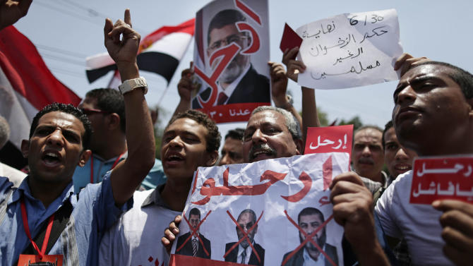 """Opponents of Egypt's Islamist President Mohammed Morsi hold posters with Arabic that reads, """"Leave, the people want the fall of the regime,"""" during a protest outside the presidential palace in Cairo, Egypt, Sunday, June 30, 2013. Thousands of Egyptians demanding the ouster of Egypt's Islamist president are gathering at Cairo's central Tahrir Square at the start of a day of massive, nationwide protests many fear could turn deadly. (AP Photo/Hassan Ammar)"""