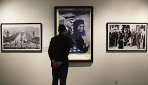 """Assistant curator looks at display of the flag that draped casket of U.S. President John F. Kennedy at the press preview of the special exhibition """"A Nation Remembers"""" at John F. Kenn"""