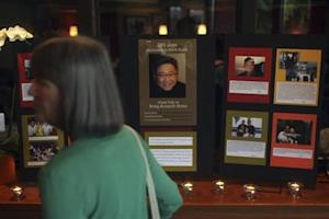 A woman walks past informational booth detailing the life of Kenneth Bae during vigil for Bae in Seattle