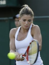 Camila Giorgi of Italy plays a shot to Nadia Petrova of Russia during a third round women's singles match at the All England Lawn Tennis Championships at Wimbledon, England, Friday, June 29, 2012. (AP Photo/Kirsty Wigglesworth)