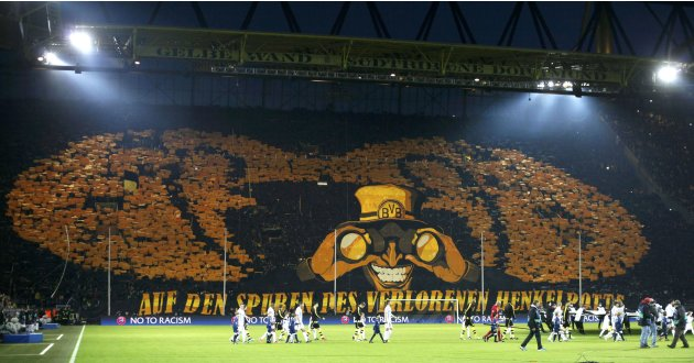 Borussia Dortmund fans hold up placards and banner before Champions League quarter-final second leg soccer match against Malaga in Dortmund