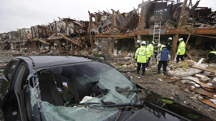 A destroyed car sits as firefighters conduct a search and rescue of an apartment complex destroyed by an explosion at a fertilizer plant in West, Texas, Thursday, April 18, 2013.  A massive explosion at the West Fertilizer Co. killed as many as 15 people and injured more than 160, officials said overnight.  (AP Photo/LM Otero)