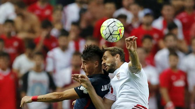 Sevilla's Fernando Llorente jumps for the ball next to Atletico Madrid's  Jose Maria Jimenez during their soccer match in Seville