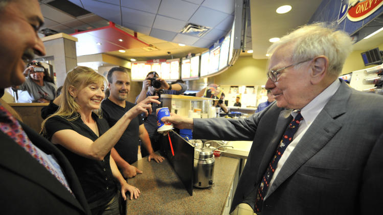 "IMAGE DISTRIBUTED FOR DAIRY QUEEN - Berkshire Hathaway's Warren Buffett, right, and Dairy Queen's CEO John Gainor, left, serves Paula Talamo, center, a S'mores Blizzard on Monday, May 20, 2013, in Omaha, Neb. Buffet helped launch the ""The First S'mores Blizzard of Summer"" and was celebrated as Dairy Queen's number one fan. (Dave Weaver/AP Images for Dairy Queen)"