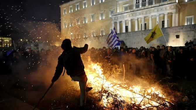 A protester is seen by a fire set by angry farmers outside the parliament during a protest against planned pension reforms in Athens