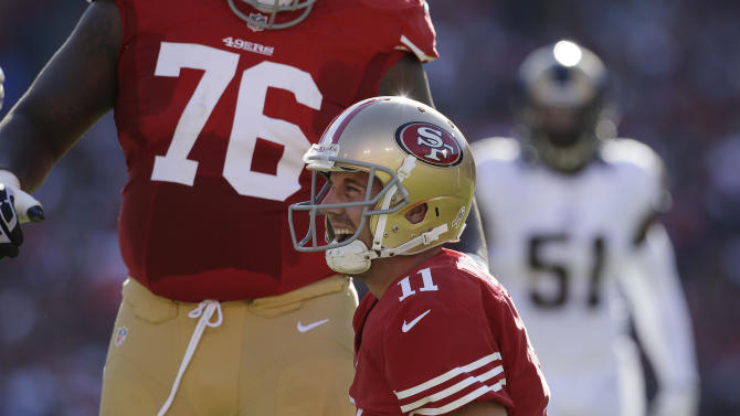 San Francisco 49ers quarterback Alex Smith is shown on the ground after being hit during the first quarter of an NFL football game against the St. Louis Rams in San Francisco, Sunday, Nov. 11, 2012. In the background is San Francisco 49ers tackle Anthony Davis at left and at right is St. Louis Rams linebacker Mario Haggan. Smith later left the game. (AP Photo/Jeff Chiu)