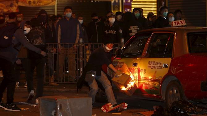 A protester sets fire beside a parking taxi at Mongkok district in Hong Kong