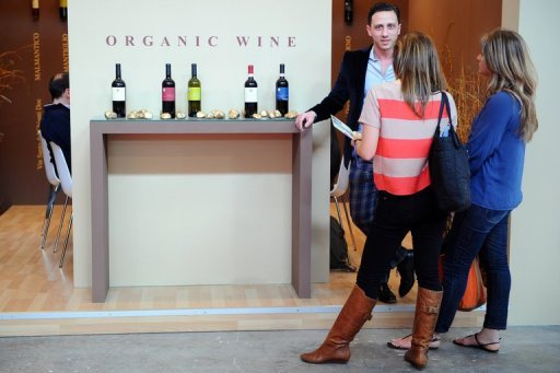 Visitors listen to an exhibitor (L) presenting organic wine in March 2012 at the Vinitaly exposition