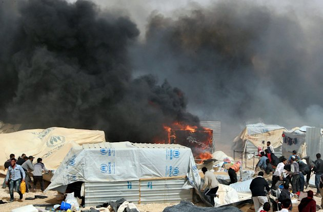 Syrian refugees extinguish a fire at the Al Zaatari Syrian refugee camp