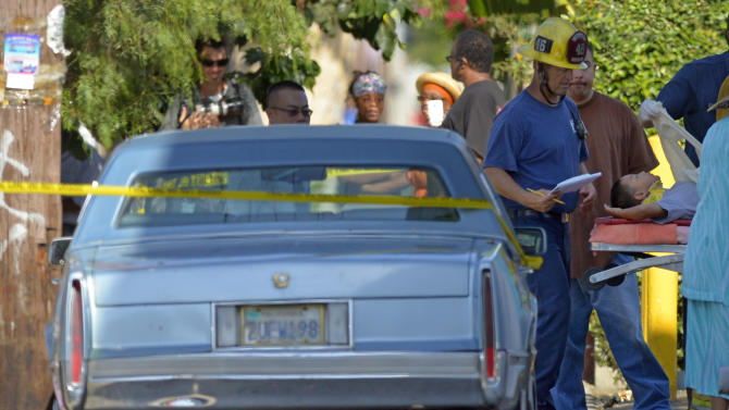 A young victim is treated by Los Angeles city firefighters after a car driven by a 100-year-old went onto a sidewalk and plowed into a group of parents and children outside a South Los Angeles elementary school, Wednesday, Aug. 29, 2012, in Los Angeles. Nine children and two adults were injured in the wreck. (AP Photo/Mark J. Terrill)