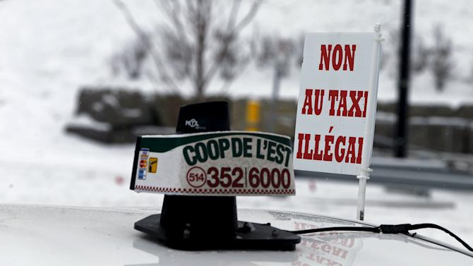 "A sign saying ""no to illegal taxis"" is seen on top of a taxi taking part in protest against Uber in Montreal"