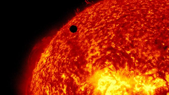 This image provided by NASA shows the Solar Dynamic Observatory's ultra-high definition view of Venus, black dot at top center, passing in front of the sun on Tuesday, June 5, 2012. The next transit of Venus won't be for another 105 years. (AP Photo/NASA/Solar Dynamic Observatory)