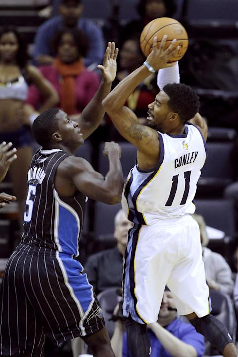 Memphis Grizzlies' Mike Conley (11) passes over Orlando Magic's Victor Oladipo (5) in the first half of an NBA basketball game in Memphis, Tenn., Monday, Dec. 9, 2013