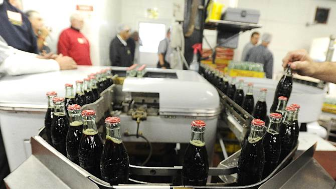 FILE - In this Tuesday, Oct. 9, 2012, photo, bottles in the last run are prepared for crates at the Coca-Cola Bottling Company in Winona, Minn. Nearly 6,000 6.5-ounce returnable glass bottles were filled for the last time after 80 years of production. (AP Photo/Winona Daily News, Andrew Link)