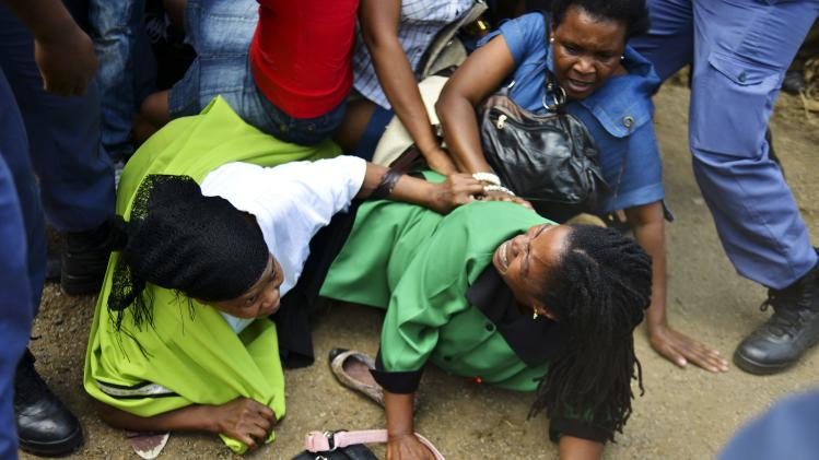 Mourners fall in a stampede as they run to queue before boarding buses to take them to the Union Buildings in Pretoria