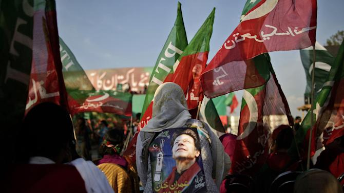 Pakistani supporters of former cricket star-turned-politician, and leader of Pakistan Tehreek-e-Insaf party, Imran Khan, wave his party's flag during a rally in Islamabad, Pakistan, Thursday, May 9, 2013. Pakistan is scheduled to hold parliamentary elections on May 11, the first transition between democratically elected governments in a country that has experienced three military coups and constant political instability since its creation in 1947. The parliament's ability to complete its five-year term has been hailed as a significant achievement. (AP Photo/Muhammed Muheisen)