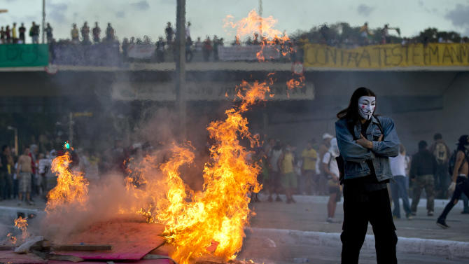 A protester with a mask stands by a burning barricade during a demonstration in Belo Horizonte, Brazil, Wednesday, June 26, 2013. Brazilian anti-government protesters in part angered by the billions spent in World Cup preparations and police clashed Wednesday near the stadium hosting a Confederations Cup football match, with tens of thousands of demonstrators trying to march on the site confronting police firing tear gas and rubber bullets.(AP Photo/Victor R. Caivano)