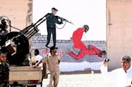 Libyan security guards are pictured in front of a mural painting depicting a torture scene outside Tripoli's Abu Slim jail, where a masscare of 1,200 prisoners took place in 1996