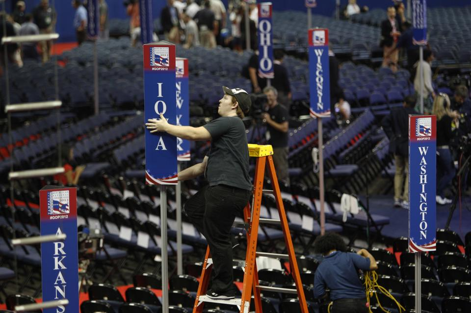 Scott Kiss of Tampa, Fla. installs an Iowa delegate sign on the floor of the Republican National Convention inside of the Tampa Bay Times Forum in Tampa, Fla., on Sunday, Aug. 26, 2012. (AP Photo/Lynne Sladky)