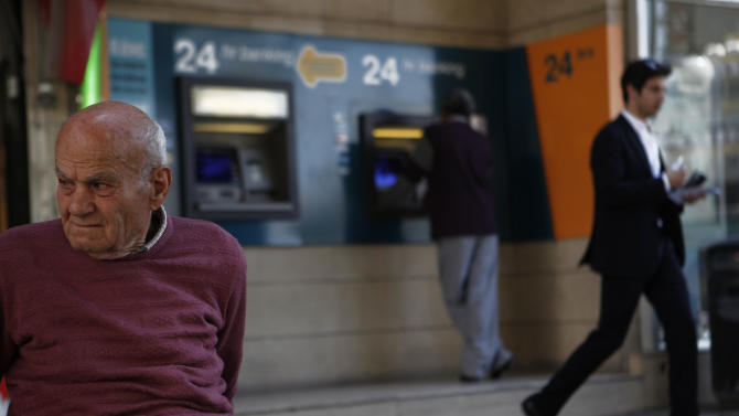 "A man, left, sit at a bench as behind two other men use the ATM machines of a branch of bank of Cyprus in central capital Nicosia, Cyprus, Friday, April 12, 2013. President Nicos Anastasiades said that he will dispatch letters to EU Commission President Jose Manuel Barosso and EU Council chief Herman Van Rompuy telling them of the ""need for a change of EU policy"" toward Cyprus by offering additional assistance. (AP Photo/Petros Karadjias)"