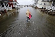 Carol Marelli walks down her flooded street Thursday, March 7, 2013, in Sea Bright, N.J., after an overnight storm. Flooding remained a problem in other shore towns. Water on roadways was also forcing closures in towns including Monmouth Beach, Absecon, Aberdeen, Egg Harbor Township and Wildwood. A coastal flood warning remains in effect until 9 a.m. Friday, but forecasters were not expecting Thursday&#39;s wind to be as strong as Wednesday, when gusts exceeding 60 mph were recorded in many places along the ocean. (AP Photo/Mel Evans)