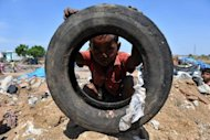 "An Indian child plays with a tire in a slum on the outskirts of Hyderabad on June 5. Population growth and unsustainable consumption are driving Earth towards ""unprecedented"" environmental destruction, the UN said in a report Wednesday ahead of the Rio Summit"