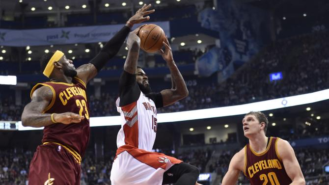 Toronto Raptors' Amir Johnson (15) drives to the basket as Cleveland Cavaliers' LeBron James (23) and Timofey Mozgov (20) defend during the first half of an NBA basketball game Wednesday, March 4, 2015, in Toronto. (AP Photo/The Canadian Press, Frank Gunn)