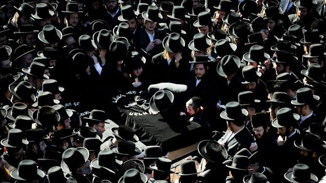 Members of the Satmar Orthodox Jewish community grieve over the coffins at the funeral for two expectant parents who were killed in a car accident, Sunday, March 3, 2013, in the Brooklyn borough of New York. A driver struck the car the couple were riding in early Sunday morning, killing both parents while their baby, who was born prematurely, survived and is in critical condition. (AP Photo/John Minchillo)