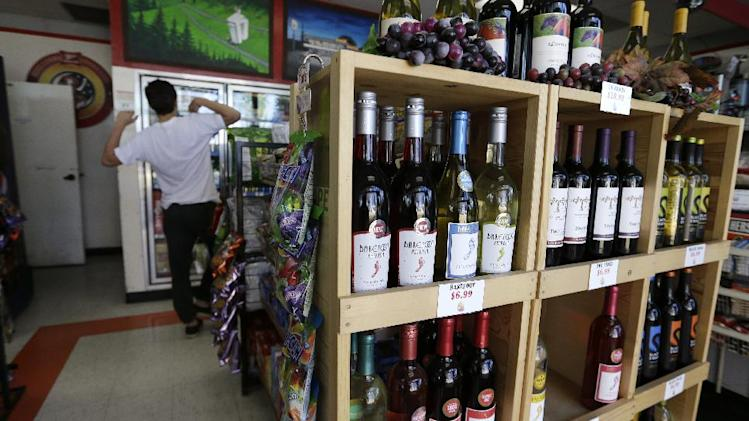 In this Thursday, May 23, 2013 photo, shelves of wine line the entrance to a gas station as a customer looks into a cooler, in Blaine, Wash. In April 2013, in its 2014 fiscal year budget proposal, the Department of Homeland Security requested permission to study a fee at the nation's land border crossings. The request has sparked wide opposition among members of Congress from northern states, who vowed to stop it. A fee, they say, would hurt communities on the border that rely on people, goods and money moving between the U.S. and Canada. (AP Photo/Elaine Thompson)