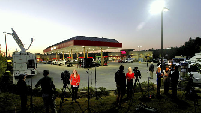 The media work at the Murphy Express gas station Thursday morning, Sept. 19, 2013, in Lexington, S.C., after the announcement that the winning Powerball ticket was sold here. Lottery officials said early Thursday that the ticket was sold at the Murphy USA station. The winning numbers drawn Wednesday night were 7-10-22-32-35 with the Powerball of 19. (AP Photo/The State, Tim Dominick)